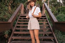 a pretty look with a white shirt, grey high waisted shorts, brown slippers, a hat and a backspack