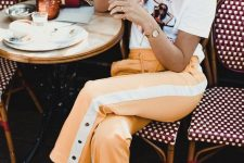 a printed t-shirt, yellow and white striped pants with buttons and leopard print sneakers