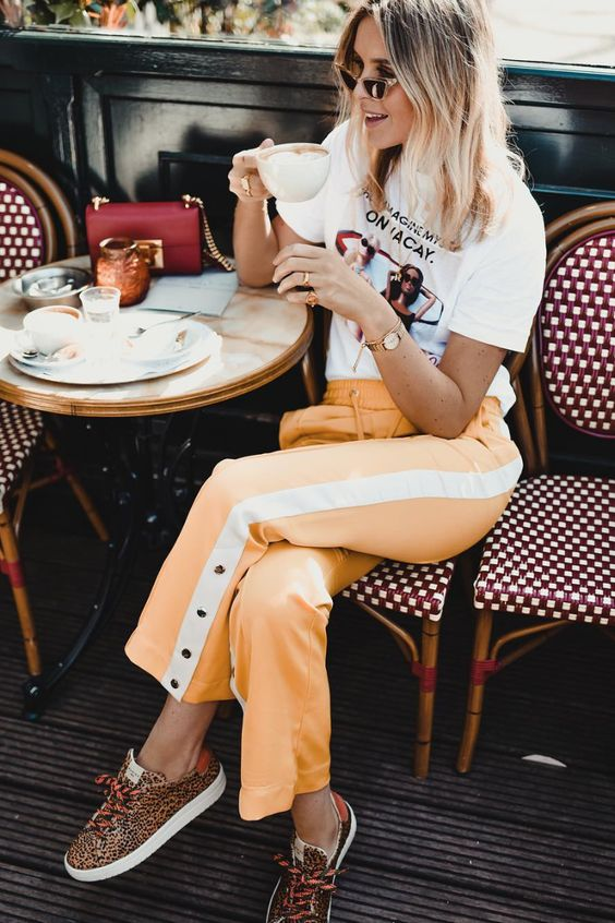 a printed t shirt, yellow and white striped pants with buttons and leopard print sneakers