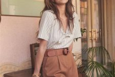 a retro-inspired summer look with a strriped shirt with a tie, rust-colored mini shorts, a brown bucket bag