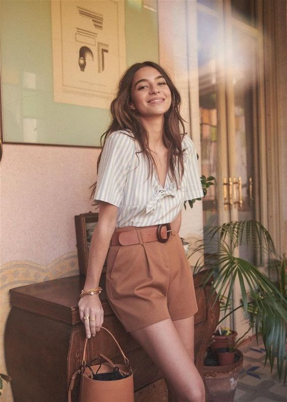 a retro inspired summer look with a strriped shirt with a tie, rust colored mini shorts, a brown bucket bag