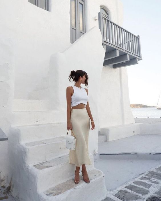a romantic look with a white crop top, an ivory slip midi skirt, nude heels and a white bag