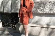 a rust-colored short suit with an oversized blazer and Bermuda shorts, a black top and black lace up heels