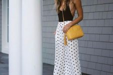 a sexy outfit with a black bodysuit with a deep neckline, white polka dot culottes, sheer heels and a yellow bag