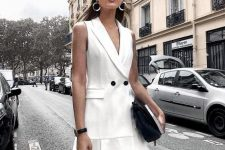 a sleeveless waistcoat dress with black buttons, a black bag, a cap, statement earrings for a summer work look