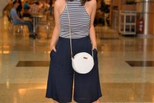a striped halter neckline top, navy bermuda shorts, grey shoes and a white round bag