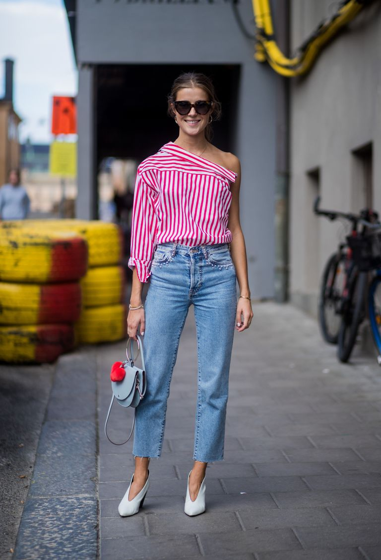 a striped one shoulder shirt, blue cropped jeans, white shoes and a blue bag with a fluff