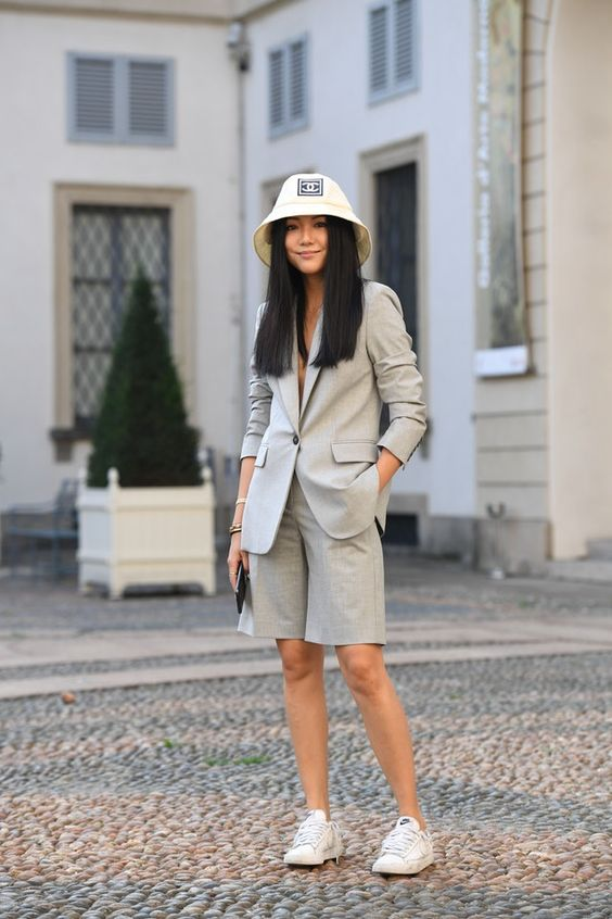 a suit with bermuda shorts and a blazer, white sneakers, a bucket hat and a clutch
