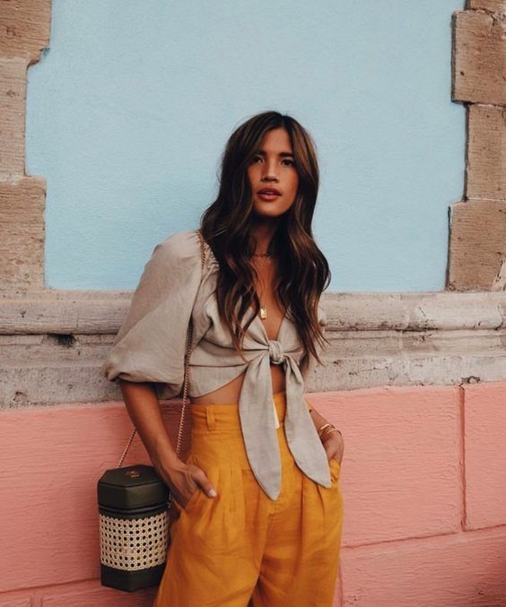 a summer look with a grey tie up blouse with puff sleeves, bright yellow high waisted pants, a whimsy black bag with a rattan insert