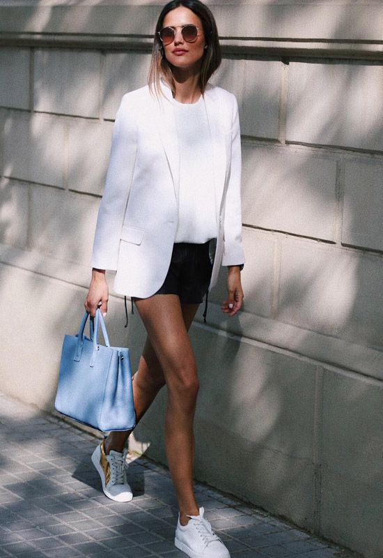 a summer look with a white t shirt, a white blazer, black mini shorts, white sneakers and a blue bag