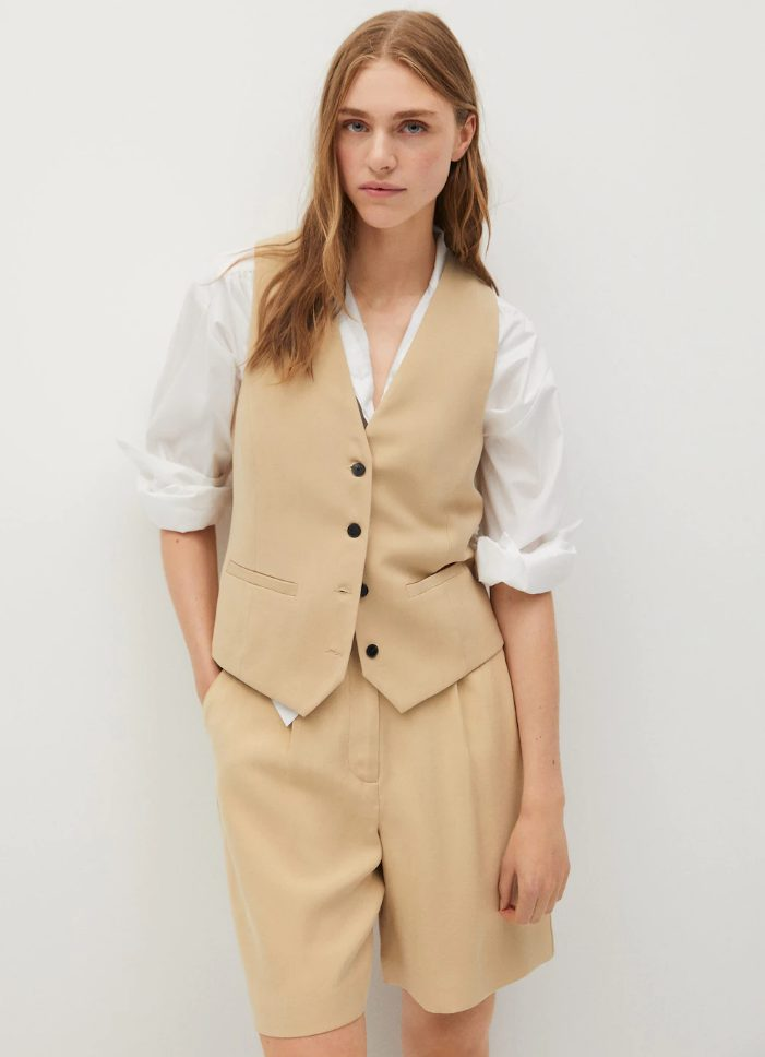 a tan Bermuda short suit with a waistcoat and a white shirt for work
