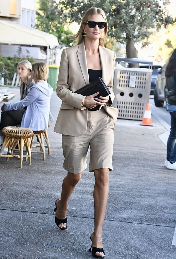 a tan short suit with a fitting blazer, Bermuda shorts, a black top and heels and a black clutch