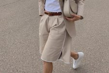 a tan short suit with a fitting blazer and Bermuda shorts, white sneakers and a white t-shirt plus a tan bag