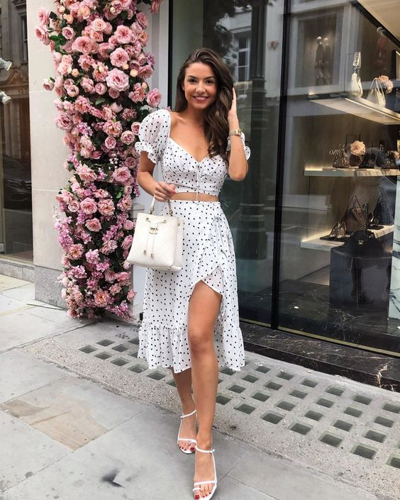 a two piece polka dot dress with a crop top and a slip skirt with ruffles, white sandals and a white bag
