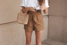 a vacation look with a white t-shirt, rust-colored paperbag waist shorts, sheer slippers and a straw bag