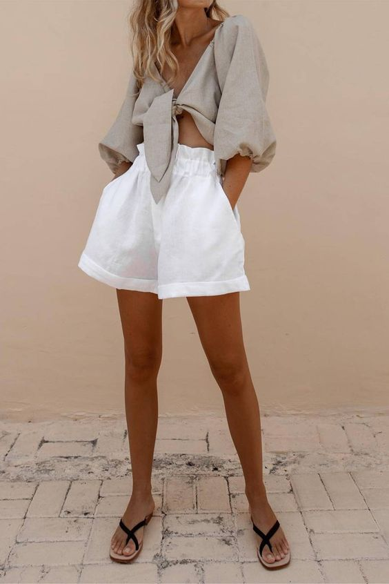 a vacation outfit with a grey linen tied up blouse with puff sleeves, white mini shorts and black slippers