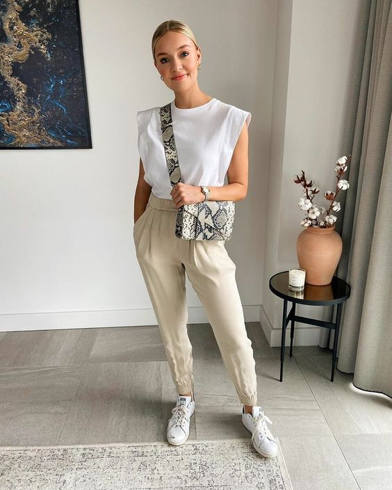 a white accented shoulder top, creamy pants, white sneakers and a snakeskin bag