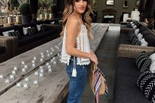 a white crochet and linen top with tassels, blue jeans, brown slippers and a straw bag for summer