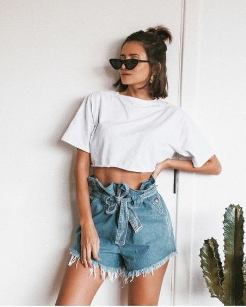 a white cropped t shirt, blue high waisted shorts and trendy sunglasses for a bold look
