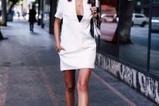 a white minimalist over the knee dress with a deep cut and short sleeves, white lace up shoes and a black and white bag