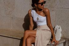 a white one shoulder top, a tan button up midi skirt, white strappy kitten heels and a beaded bag