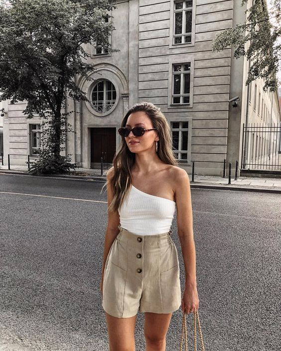 a white one shoulder top, linen high waisted button up shorts, a straw bag and sunglasses