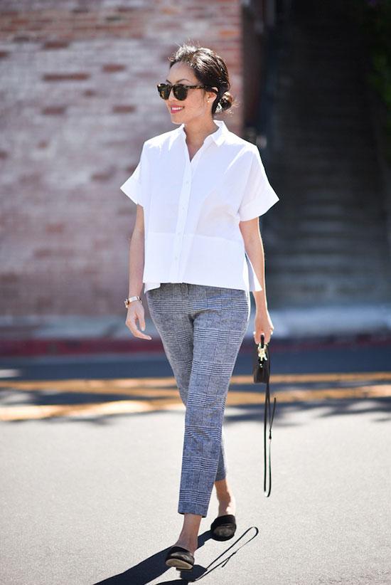 a white oversized short-sleeved shirt, grey plaid cropped pants, black slippers, a black mini bag