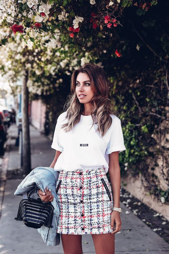 a white oversized tee, a tweed mini skirt, a denim jacket and a whimsical bag