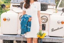 a white polo mini dress, white sneakers, a blue jumper and a navy round bag for a simple and classic look