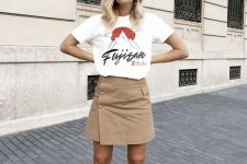 a white printed t-shirt, a tan button up mini skirt, black square toe shoes for a simple and bold look