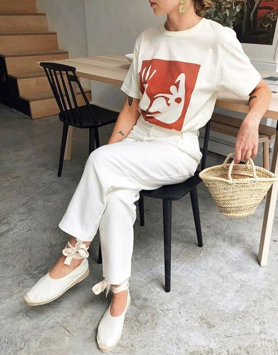 a white printed t-shirt, neutral jeans, white espadrilles, a mini straw bag and statement accessories