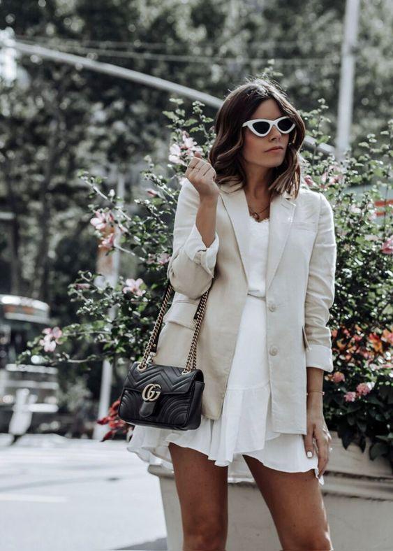 a white ruffle mini dress, a neutral linen blazer, a black bag and retro-inspired sunglasses for summer