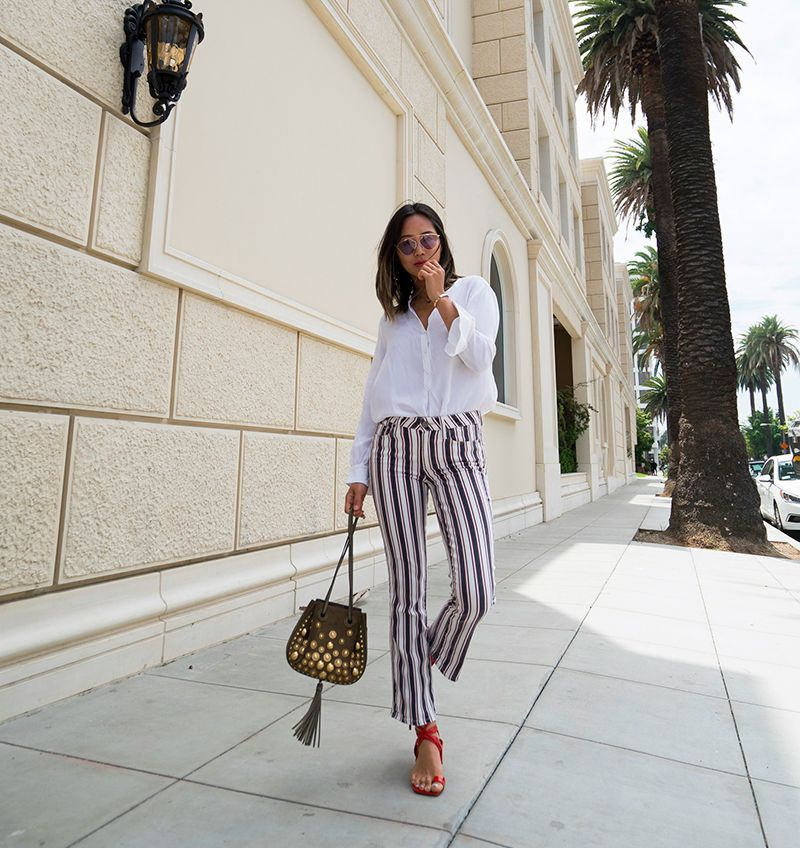 a white shirt, striped pants, red ankle strap sandals and a whimsical embellished bag