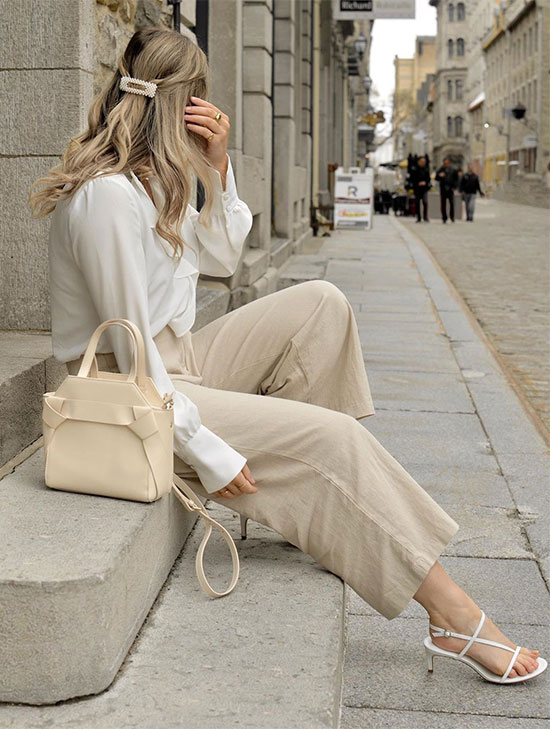 a white shirt, tan wideleg pants, white strappy heels and a tan bag for a chic and elegant look