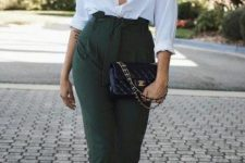 a white shirt with a deep neckline, dark green high waisted pants, white embellished shoes and a black bag