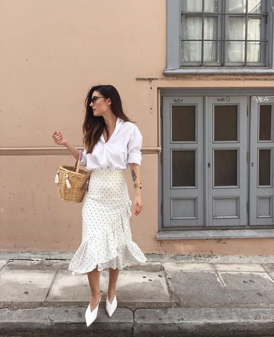 a white shirt with cuffed sleeves, an ivory polka dot ruffle skirt, white shoes and a basket