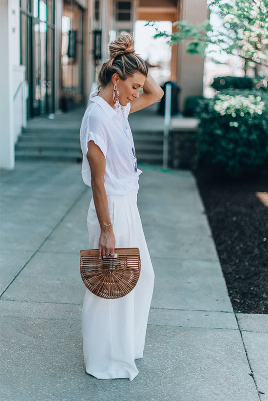 a white shirt with short sleeves, white palazzo pants, statement earrings and a wooden bag for much comfort