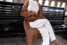 a white sleeveless halter neckline top, wideleg pants, silver shoes, a brown clutch and a duster