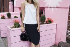 a white sleeveless top, a black knee skirt with slits, black bow mules and a black mini bag