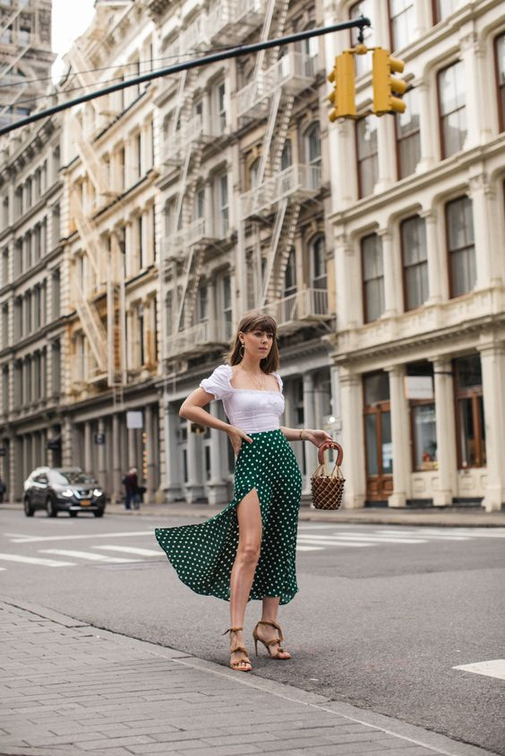 a white square neckline top, a green polka dot midi with a thigh high slit, nude heels and a bucket bag