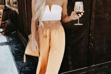 a white strapless crop top, yellow linen wideleg pants, a tan bag and sunglasses for a summer brunch