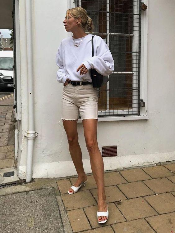 a white sweatshirt, tan mini shorts, white kitten heel sandals, a black bag