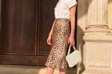 a white t-shirt, a leopard print midi, black kitten heel sandals, a beaded bag