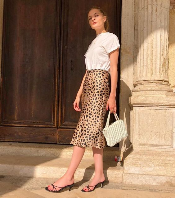 a white t shirt, a leopard print midi, black kitten heel sandals, a beaded bag