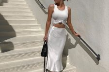 a white tied up top, a pearly slip midi skirt, white strappy kitten heels and a black bag