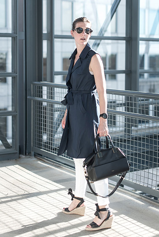 a white top, white pants, a black sleeveless trench, black espadrilles and a black bag for summer