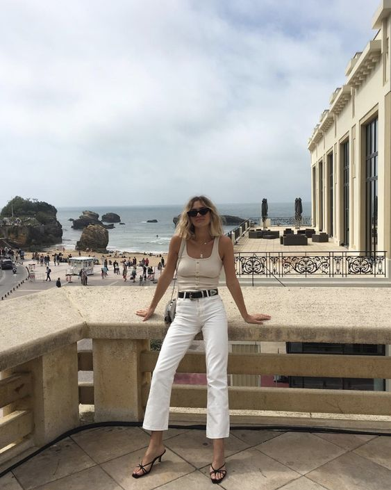 an ivory button up top, white jeans, black strappy kitten heel sandals and a black belt