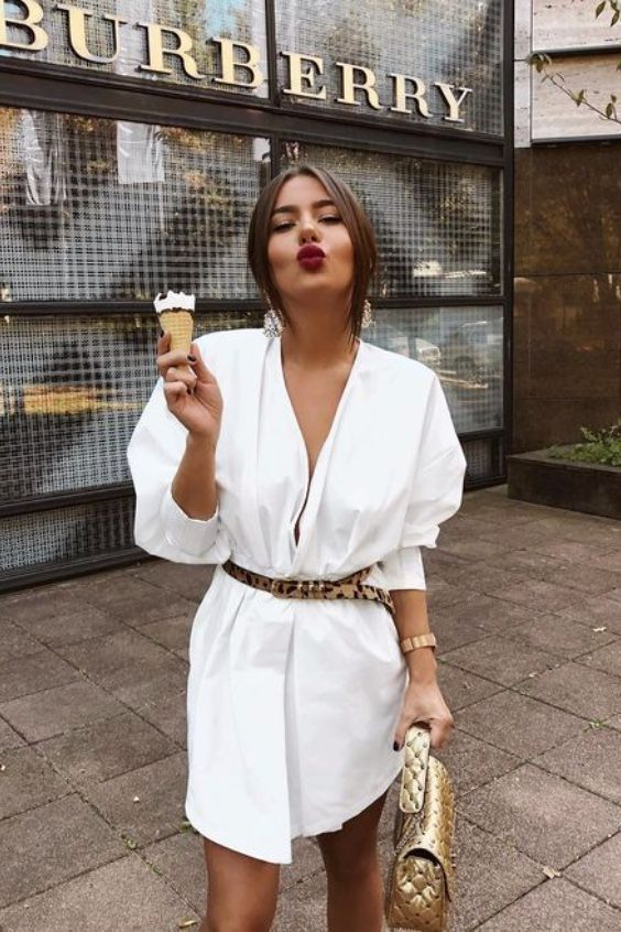an oversized white shirtdress, an animal print belt, a metallic bag, statement earrings and a red lipstick