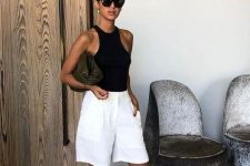 an ultra-minimalist look with a black halter neckline top, white bermuda shorts, black heels and a clutch