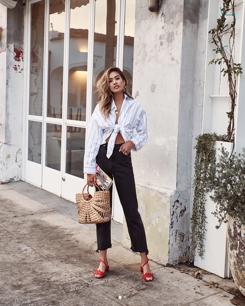 black jeans, a white oversized tied up shirt, red heels and a straw bag